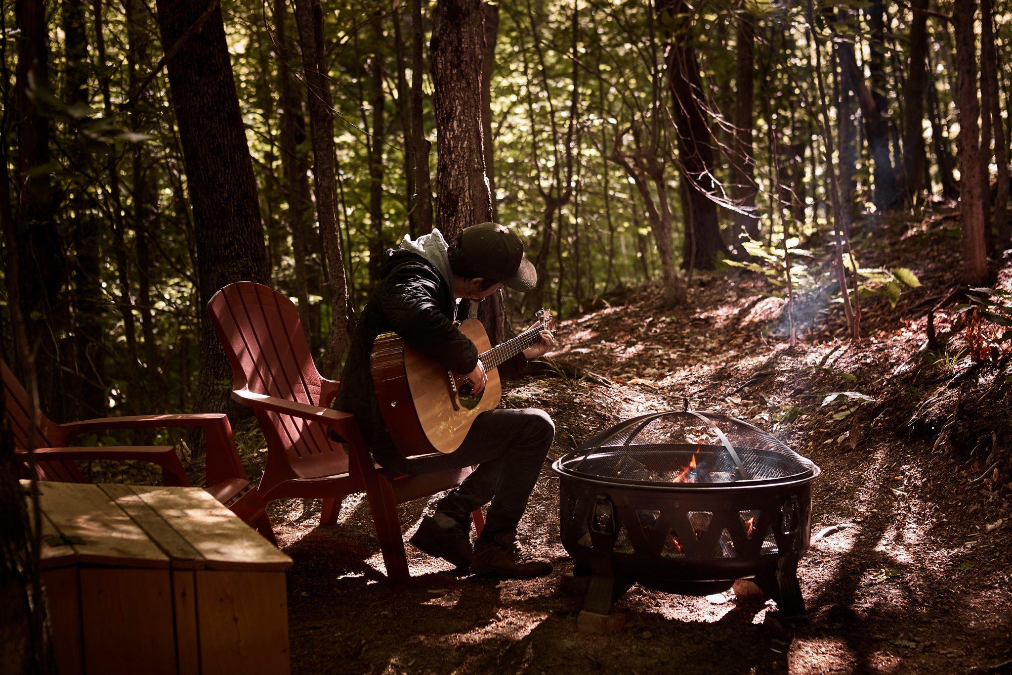 Une personne qui joue de la guitare durant un séjour de glamping à la Station du Chêne rouge