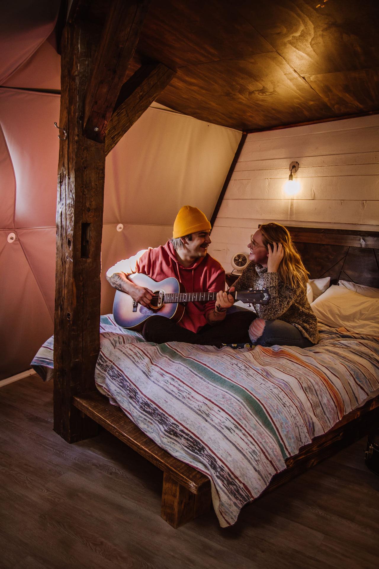 Deux personnes qui jouent de la guitare sur un lit - Glamping Cielo