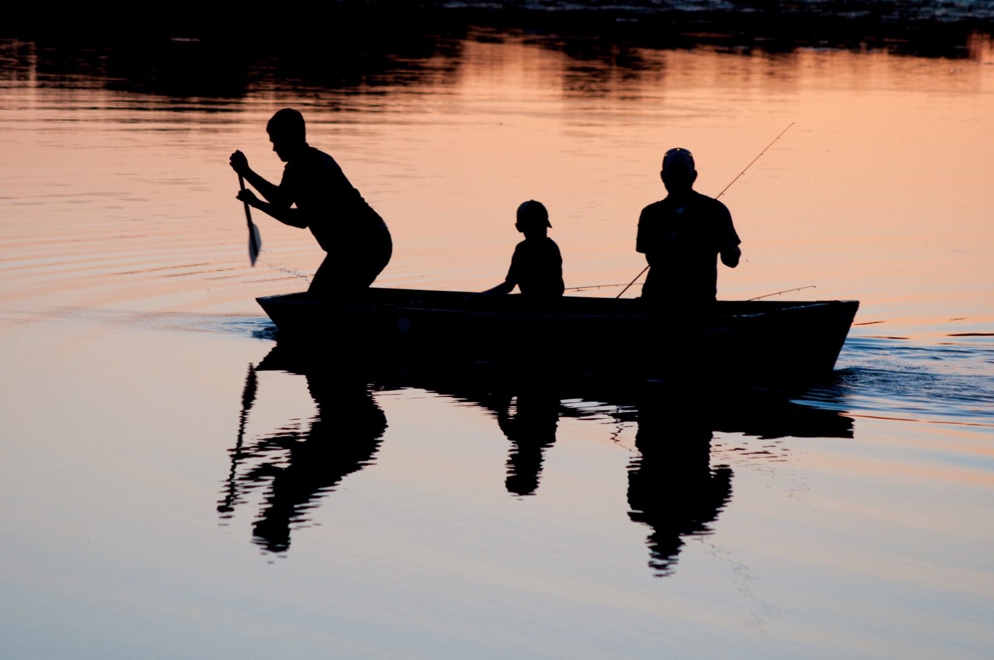Silhouettes d'une famille qui pratique la pêche